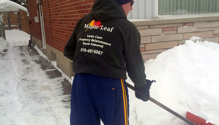 maple leaf lawn maintenance employee in branded black sweater shoveling snow at residential property