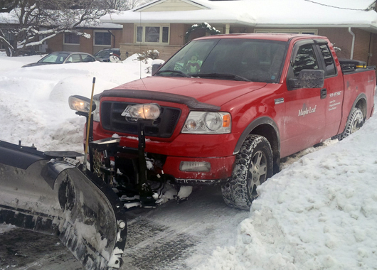 red maple leaf lawn maintenance truck with snow plow slider backed into residential driveway