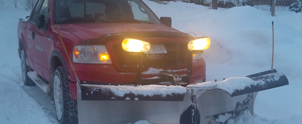 red maple leaf lawn maintenance truck with snow plow slider and bright lights fixed to the front