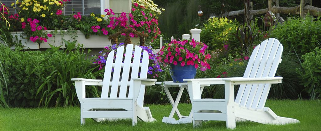 Two lawn chairs in a beautiful garden with colourful flowers