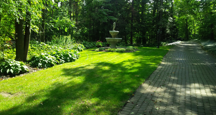 nicely cut lawn with cobblestone path way and multi-level water fountain in the background